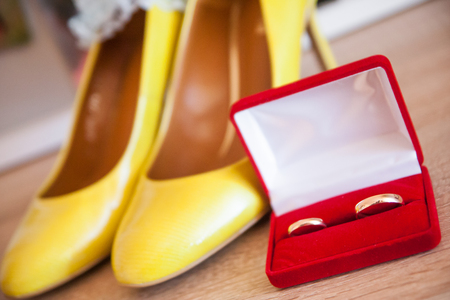 Golden wedding rings in red box with yellow shoes.