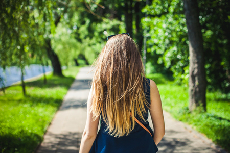 Young student girl walking in a park by the lake.
