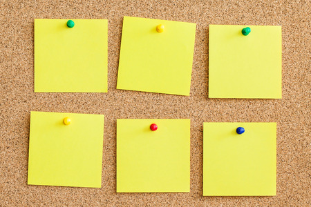 Blank empty copy space square papers background. Yellow memo reminder cards pinned to cork board.