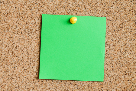 Cork board with green memo reminder card attached with yellow pin.