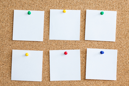 Six white memo cards reminder pinned to cork board. Blank empty copy space square papers background. Stock Photo
