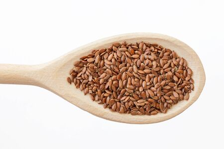 Flax seed on wooden spoon closeup macro food background. Banque d'images
