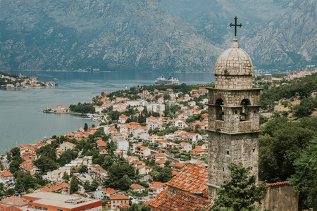 Kotor bay in Montenegro cityscape and landscape. Beautiful view from high hill next to the city. Old church tower with roof tops in the background.