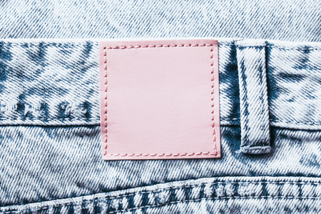 Pink leather blank copy space label on blue jeans denim background. 스톡 콘텐츠