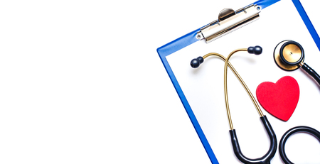 Stethoscope and red heart shape on clipboard with paper isolated on white. Horizontal medical empty copy space.