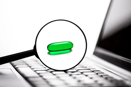 Magnifying glass on laptop keyboard. Science and medical research green pill isolated on white. Imagens