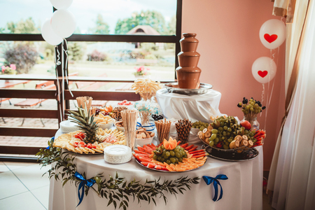 Sweet catering table with chocolate fountain and fruits. Wedding venue decorations.
