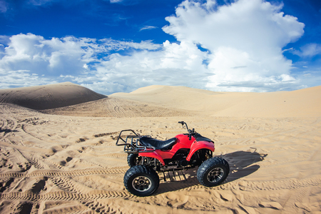 Red atv quad in desert sand with blue cloudy sky in the background. Imagens