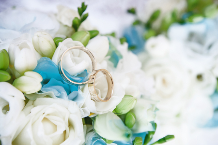 Two golden wedding rings on white and green flowers bouquet.