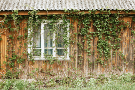 Rustic window in wooden village cottage house. Grunge weathered, brown wood wall background.