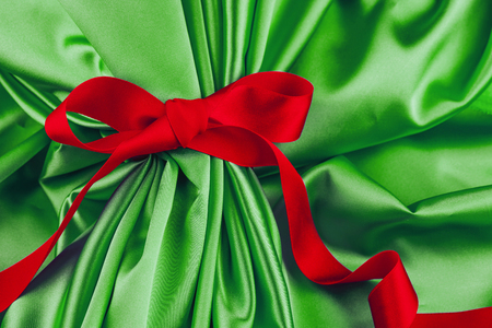Green satin fabric with red ribbon. Gift present background.