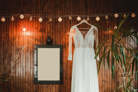 White wedding dress hanging on wooden wall background.
