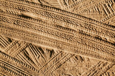 Tire mark shape lines on dry yellow sand pattern.