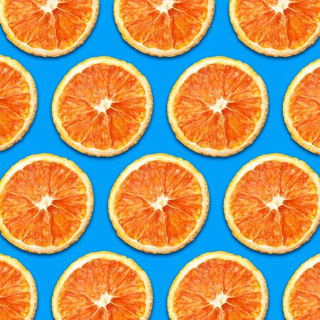Dry orange slices isolated on blue background. Pattern design. Archivio Fotografico