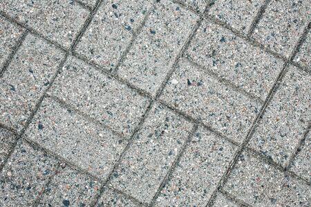 Pavement gray mosaic brick blocks background. Grunge dirty road texture.
