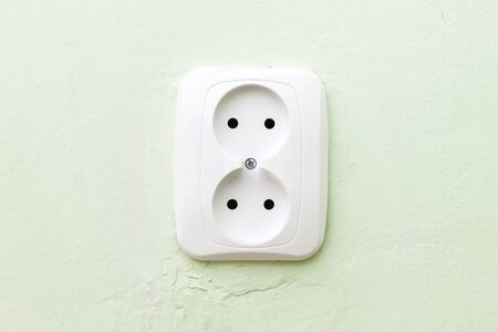 Simple white electrical socket on house wall closeup. Empty copy space electricity symbol background. 스톡 콘텐츠