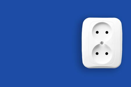 White electric outlet isolated on blue. Empty copy space electricity socket background.