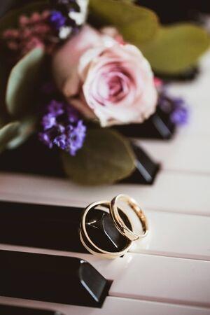 Piano keyboard backdrop. Golden wedding rings. Symbol of love. Love music background. White and black keys. Zdjęcie Seryjne