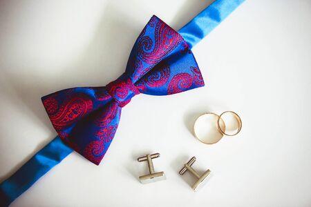 Wedding groom fashion. Bow tie, cufflinks and golden rings background. Elegant wedding accessory background.