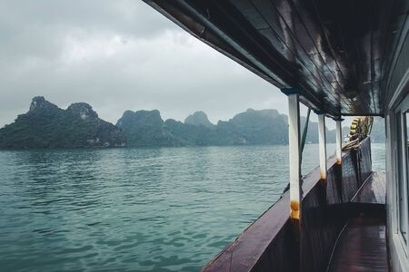 Halong bay boat cruise background. Low season cloudy day. View from the deck of the ship.