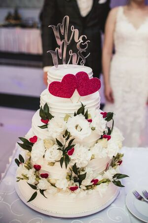 Wedding cake. Bride and groom in the background. Sweet dessert decorated with heart symbol and flowers. Wedding reception tradition. Mrs and Ms on the top.