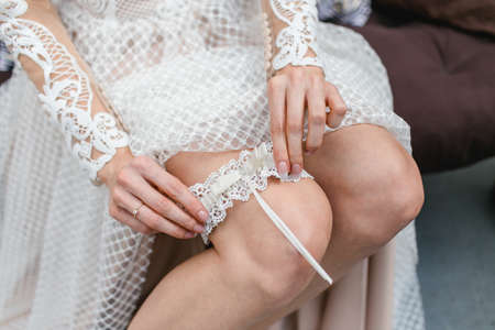 Wedding garter background. Young bride getting ready for ceremony. Dressing up white wedding dress. Bridesmaid help and support.