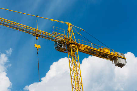 Empty copy space crane background. Yellow paint heavy machinery equipment isolated on blue cloudy sky. Construction site view. Industrial building process.