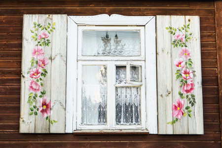 Wooden window background. Rustic cottage house. Vintage cabin wall. Poland countryside architecture texture. Open window shutters decorated with floral pattern.