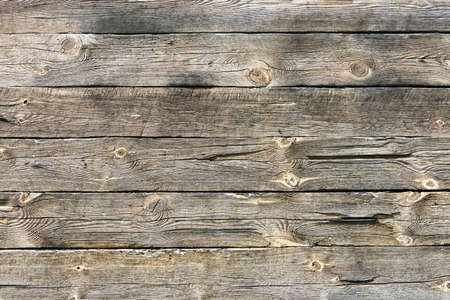 Raw natural wood texture. Gray wooden wall background. Rustic desks with knots pattern. Countryside architecture wall. Village building construction.