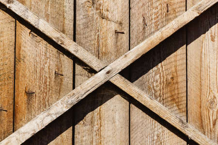 Wooden barn door. X shape wooden desks. Rustic nails vintage desk construction background. Countryside architecture texture. Village building farm door entrance.