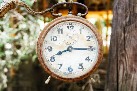 Vintage rusty clock. Time retro background. Grunge mechanical watch. Antique machine hanging outdoor.