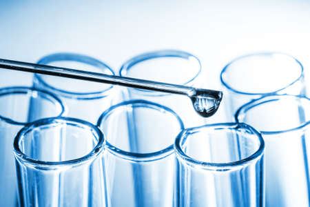 Laboratory test tube background. Covid-19 corona virus pandemic crisis. Glass pipette fluid drop. Global disease problem. Vaccine research science texture. Shiny crystal glass isolated on white. Banco de Imagens