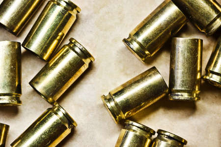 Bullet shells background. Metal shiny 9mm ammo glock 19 shells. Vintage parchment paper. Weapon shooting texture. Crime scene background. Stock Photo