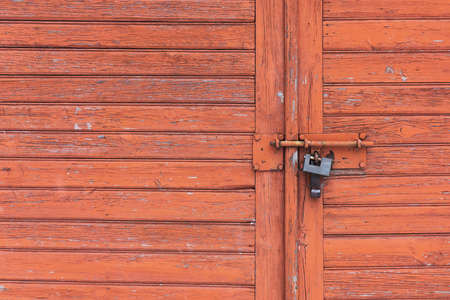 Wooden garage door. Metal padlock background. Peeling paint wood. Vintage rustic gate. Empty copy space grunge door texture.