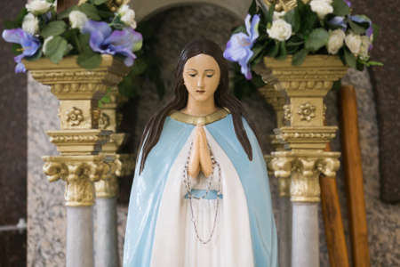 Mother Mary pray. Blessed virgin statue. Rosary in hands.