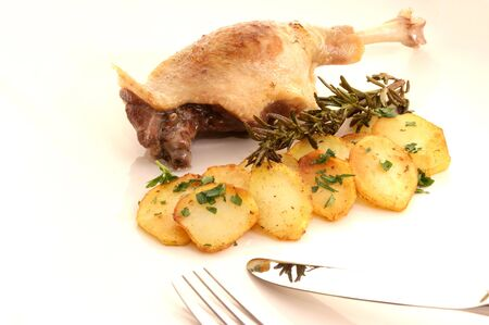 Roasted duck leg and potatoes photo