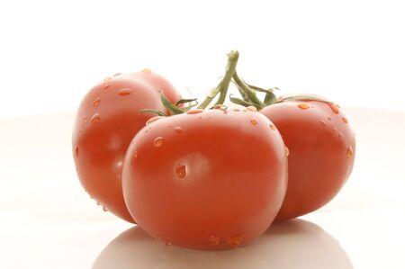 tomatos: three fresh tomatos on a white background