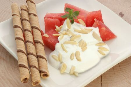 melon with cream fresh and almond slivers and biscuit photo