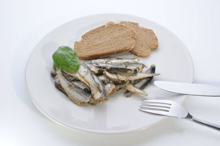 sprats: some sprats and bread on a white plate