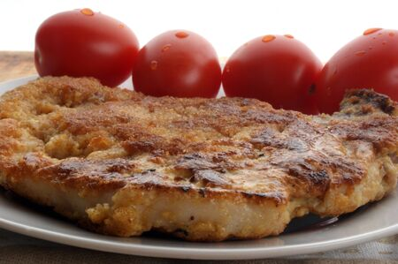 one pork cutlet and tomato on a plate Stock Photo - 5813603