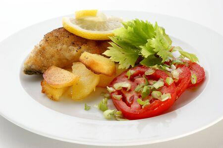 carp steak with potato and organic tomato photo