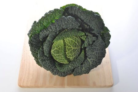 savoy cabbage: organic savoy cabbage on a timber board Stock Photo