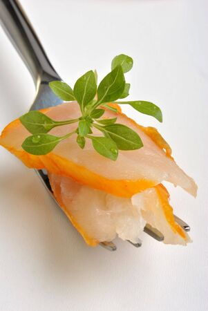 some fresh smoked salmon on a fork with greek basil