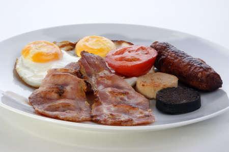 irish breakfast on a white plate with tomato photo