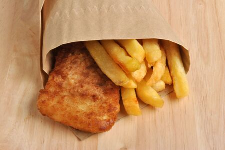 fish and chips on a timber board photo