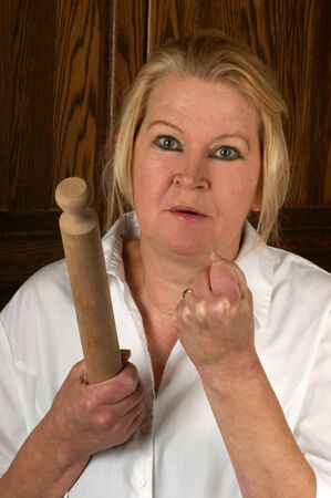alarmed: upset mature woman holds a rolling pin Stock Photo
