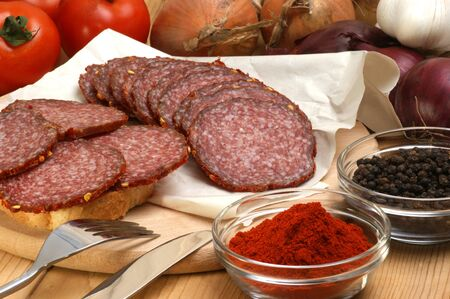 salami and some slices salami on a timber board