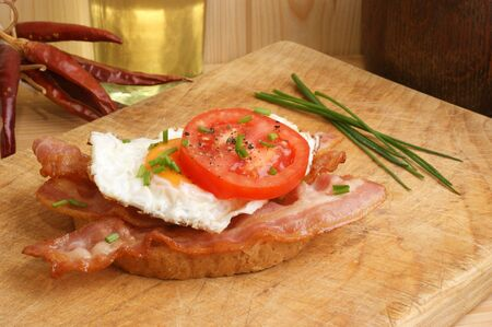 tomatoe bread with some bacon and fried egg photo