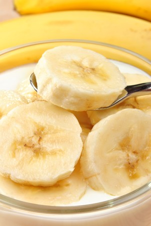 eating banana: some organic banana slices  in natural yoghurt