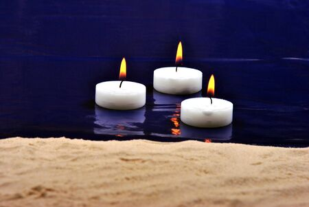 swimming candles: some candles swimming in the blue water Archivio Fotografico